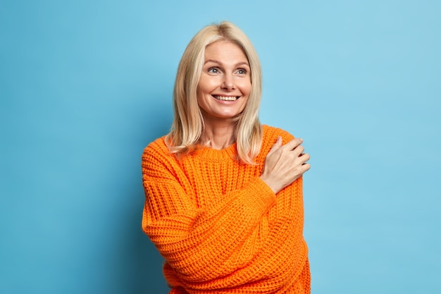 Satisfied blonde middle aged woman has dreamy expression smiles gently and thinks about something pleasant wears comfortable knitted sweater.
