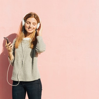 Satisfied blonde young woman enjoying the music on mobile phone through headphone against pink backdrop