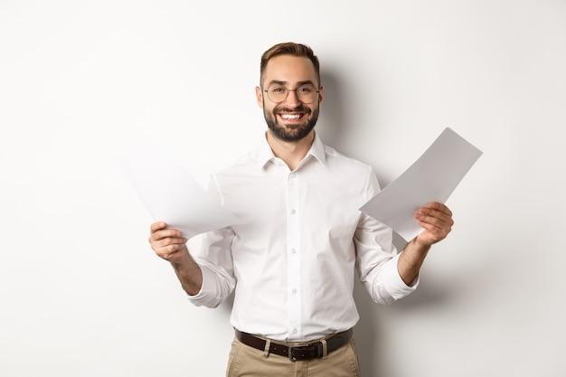 Довольный босс улыбается, держа хороший отчет, читая документы, стоя