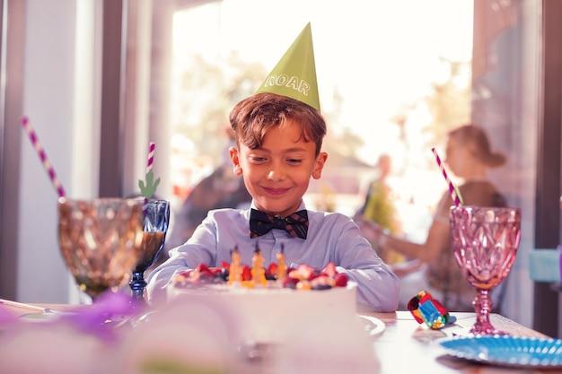 満足した少年。テーブルの上の彼のバースデーケーキを見ながら笑顔で嬉しいと感じている陽気な誕生日の男の子