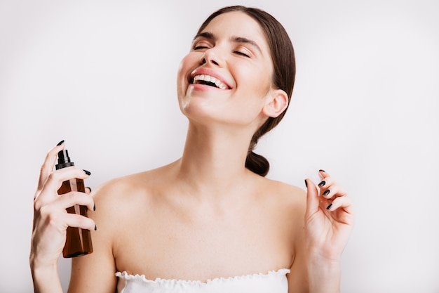 Satisfied brunette girl after shower sprays mist for body on skin. woman smiling on isolated wall.