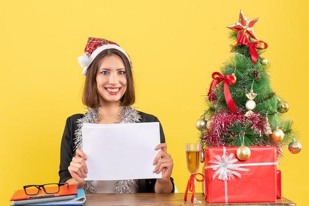 Signora di affari soddisfatta in vestito con cappello di babbo natale e decorazioni di capodanno che lavora da sola tenendo i documenti e seduta a un tavolo con un albero di natale su di esso in ufficio