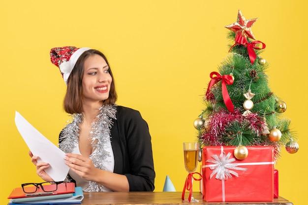 Signora di affari soddisfatta in vestito con cappello di babbo natale e decorazioni di capodanno che lavora da solo e seduto a un tavolo con un albero di natale su di esso in ufficio