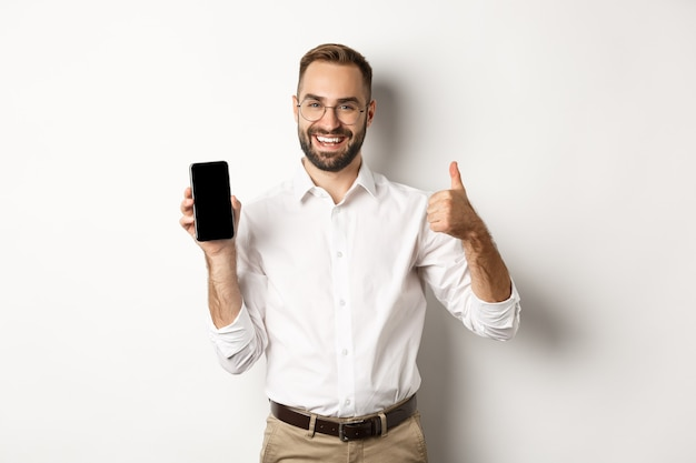 Satisfied business man in glasses showing thumbs up and demonstrating mobile phone screen, recommending app, standing over white background.