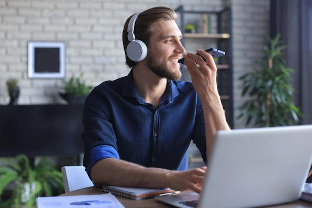 Довольный деловой человек в очках держит смартфон возле рта для записи голосового сообщения или общения в чате.