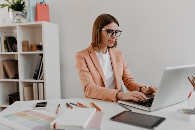 노트북에서 일하는 안경 만족 된 비즈니스 여자입니다. 사무용 가구에 세련 된 복장에 젊은 여자의 초상화.