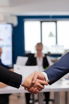 Satisfied businessman company employer wearing suit handshake in conference room , workplace