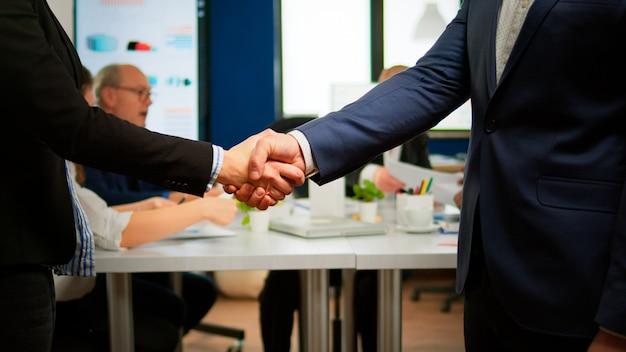 Soddisfatto datore di lavoro azienda datore di lavoro che indossa abito stretta di mano nuovo dipendente viene assunto al colloquio di lavoro, il manager delle risorse umane maschio impiega il candidato di successo stringe la mano alla riunione d'affari, concetto di collocamento