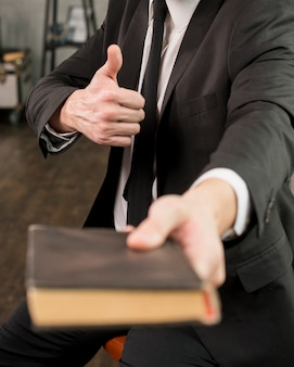 Satisfied businessman giving book showing thumb up