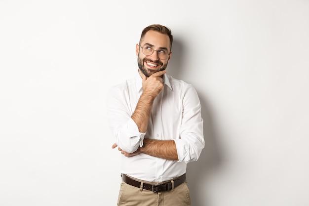 面白いアイデアを持って、左上隅を見て、幸せな笑顔で考え、白い背景の上に立って満足しているビジネスマン。