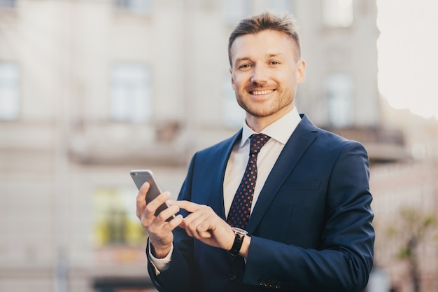 Satisfied businessman holds smart phone