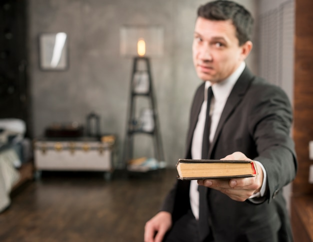 Satisfied businessman offering book