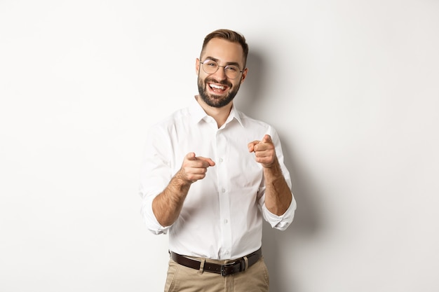 Satisfied businessman pointing fingers at camera, praising you, approve or like something, white background.