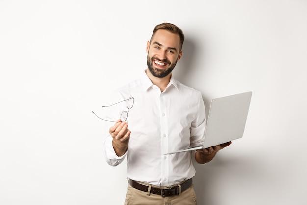 Довольный бизнесмен, хвалящий хорошую работу, проверяя ноутбук, стоя