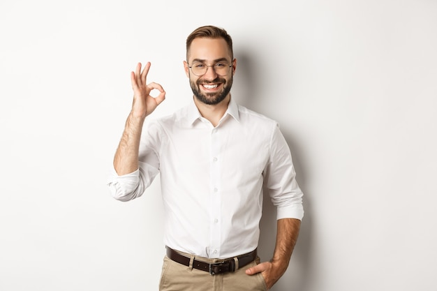 Satisfied businessman smiling and showing ok sign, approve and like something good, standing