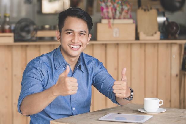 Удовлетворенный клиент кафе показывает большой палец вверх