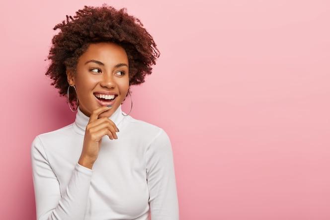 満足のいく屈託のない女性モデルは優しく微笑んで、あごに触れて、脇を見て、面白いシーンに気づき、何かを笑い、自然な巻き毛の黒い髪を持ち、カジュアルな服を着て、ピンクの壁に隔離されています