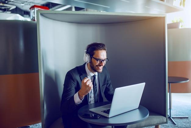 満足している白人のひげを生やした実業家のスーツで、眼鏡とヘッドフォンでラップトップを見て、職場で座っている間、素晴らしい仕事を応援します。