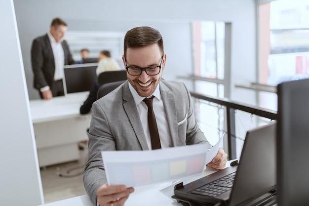 眼鏡と職場で座っている間書類を見てスーツで満足している白人の実業家。