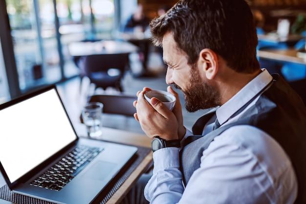 カフェに座って、コーヒーを飲みながらノートパソコンを見てスーツで満足している白人のハンサムなひげを生やした実業家。