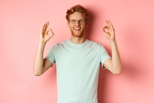 Удовлетворенный кавказский мужчина с рыжими волосами, в очках и футболке, демонстрирующий нормальные жесты и улыбающийся, говорящий «да» и что-то одобряющий, стоит на розовом фоне.