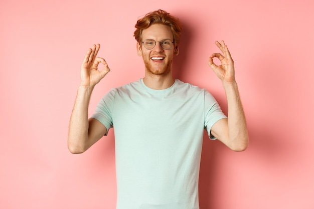 Satisfied caucasian man with red hair, wearing glasses and t-shirt, showing okay gestures and smiling, saying yes and approving something, standing over pink background.