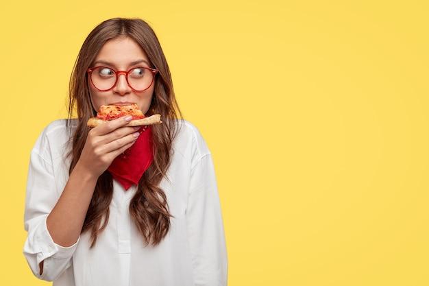 만족 한 백인 모델은 실내에서 맛있는 피자를 먹고, 점심을 먹고, 광학 안경, 흰색 셔츠와 빨간 두건을 착용하고, 슬로건이나 텍스트를위한 여유 공간이있는 노란색 벽에 서 있습니다.