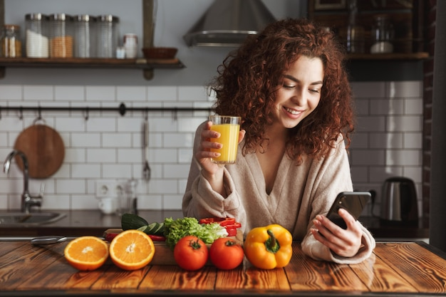 Satisfied caucasian woman using mobile phone while cooking fresh vegetables salad in kitchen interior at home