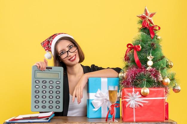 Signora affascinante soddisfatta in vestito con il cappello di babbo natale che mostra la calcolatrice nell'ufficio su colore giallo isolato