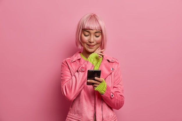 Satisfied charming woman social media blogger with stylish hairstyle, holds smartphone, reads article in internet