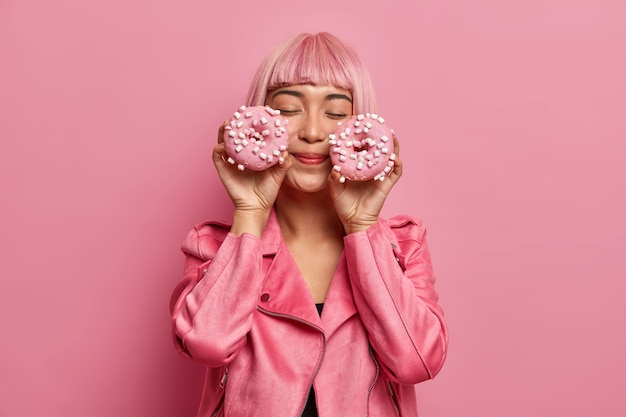 Satisfied charming woman with pink hair and fringe, closes eyes, imagines pleasant taste of donuts, dressed in rosy jacket