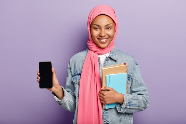 Satisfied charming young muslim woman in pink hijab on head