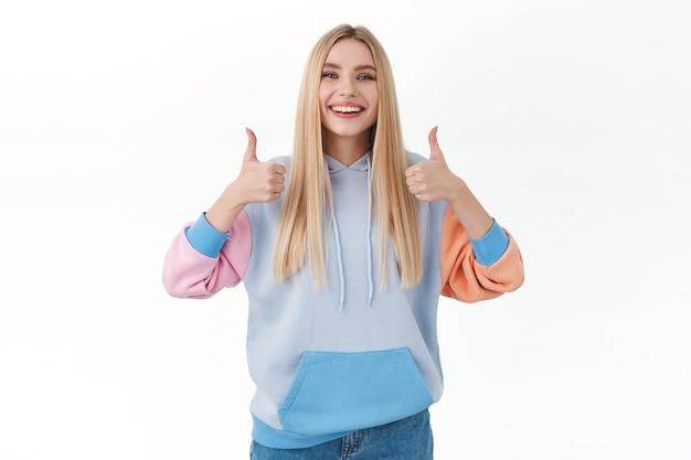 満足している陽気で魅力的なブロンドの女の子は、いいねや承認で親指を立てる