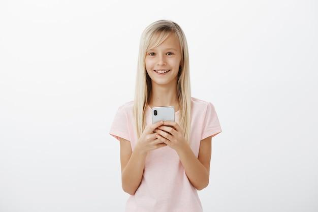 ピンクのtシャツで陽気なかわいいブロンドの女の子に満足し、高価なスマートフォンを押しながら笑顔