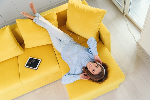 Satisfied cheerful girl lying on the comfortable couch and listens to the music on her white earphones. top view.
