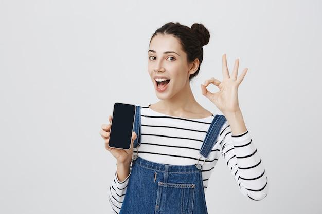 笑顔で満足している陽気な女性、大丈夫のサインと携帯電話のディスプレイを表示