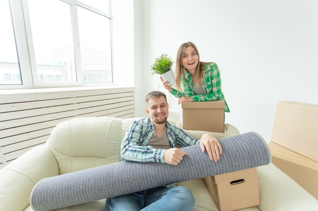 満足のいく陽気な若いカップルの強い男ときれいな女性が手に物を持っています