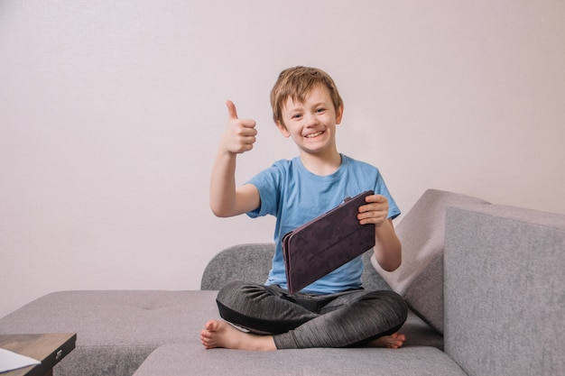 Satisfied child in a blue t-shirt plays on the couch with a tablet