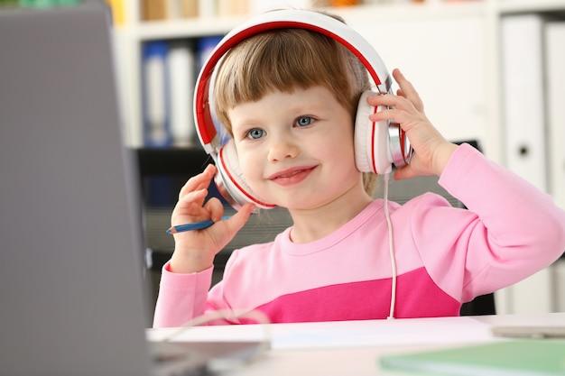 Satisfied child in headphones sitting