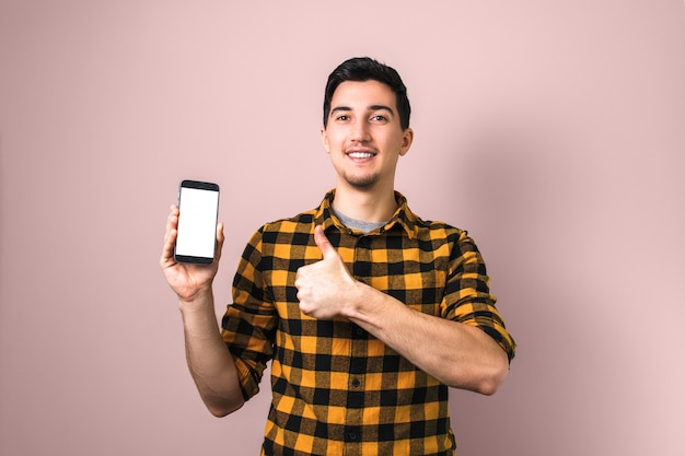 Satisfied client. man holding a phone with white screen showing big thumb up