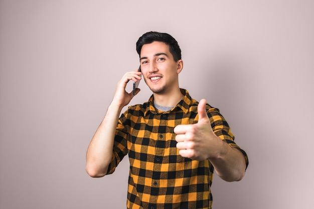 Satisfied client. man speaking on the phone showing big thumb up