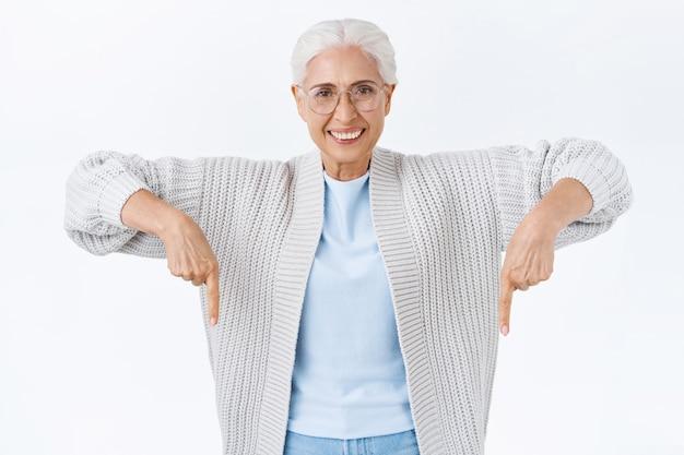 Soddisfatta, fiduciosa, felice, sorridente, donna anziana felice con i capelli grigi, con gli occhiali, che punta verso il basso per rivolgere l'attenzione fantastica vendita promozionale, mostrando il suo entusiasmo, consigliare pubblicità, fare clic sul banner
