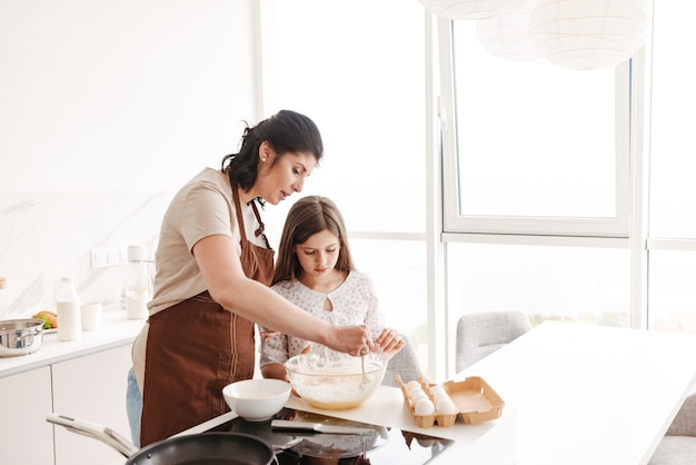 Satisfied content woman and little daughter baking pastry in kitchen at home, and kneading dough with spoon
