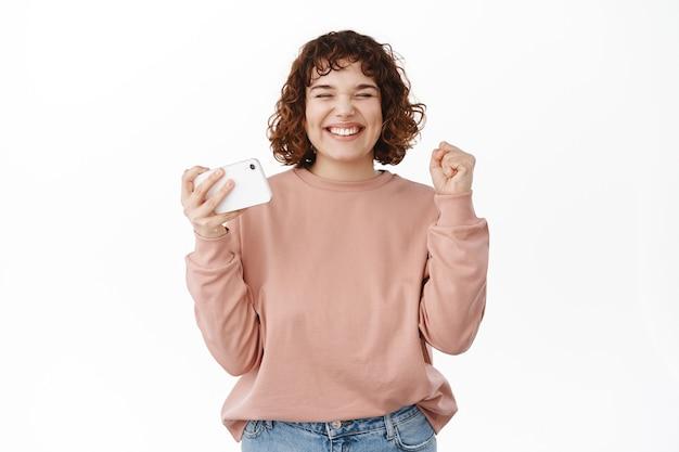 満足している巻き毛の女の子は、「はい」と言って目標を達成し、横向きのスマートフォンを持って拳ポンプを作り、ビデオゲームアプリで勝ち、白の上に立って祝います。