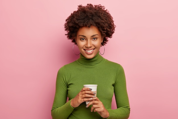 Satisfied curly woman enjoys coffee break, holds disposable cup of beverage, looks happily , wears green turtleneck, smiles joyfully, has spare time after work isolated on pink wall