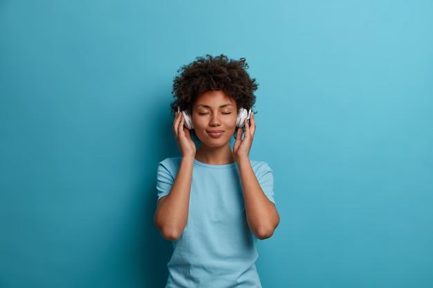 만족스러운 곱슬 머리 젊은 아프리카 계 미국인 여성은 평온한 행복 분위기를 가지고 있으며 눈을 감고 헤드폰으로 음악을 듣고 캐주얼 파란색 티셔츠를 입고 실내 포즈를 취합니다. 사람, 레저, 엔터테인먼트 개념