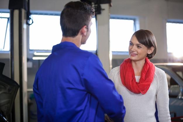 Satisfied customer shaking hands with mechanic
