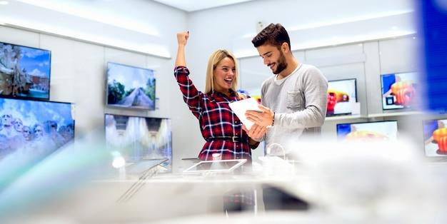 Довольные клиенты покупают планшет.