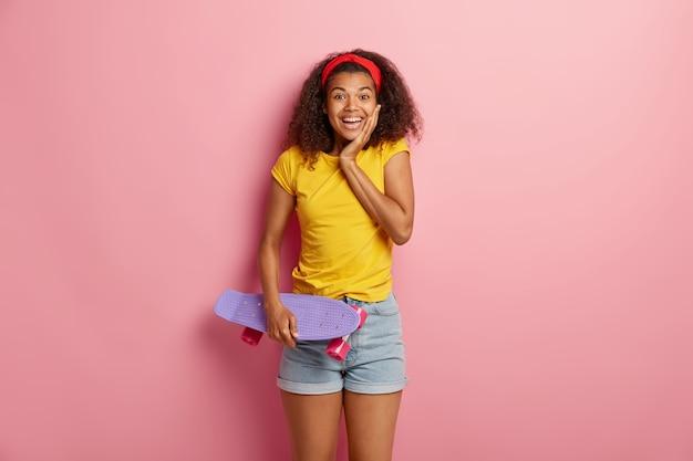 満足しているかわいいアフロの女性は運動活動をしていて、スケートボードを持っていて、リラックスして喜んでいます