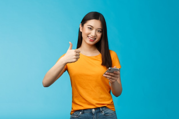 Satisfied cute asian brunette hold smartphone show thumb-up delighted, recommend awesome gadget, give approval good new app, agree friend posted good blog article, stand blue background